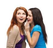Två le flickor som viskar skvaller Royaltyfri Bild