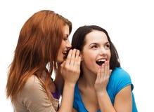 Två le flickor som viskar skvaller Royaltyfri Foto