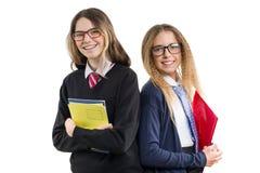 Två le högstadiumflickor i bärande exponeringsglas för likformig med anteckningsböcker poserar på en isolerad vit bakgrund arkivfoton