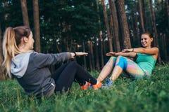 Två le idrottskvinnor som utbildar utomhus att göra fulla sitta-UPS som sitter mitt emot de på gräs i skog Fotografering för Bildbyråer