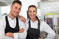 Två le kockar i kök royaltyfri bild