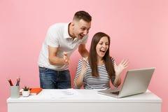 Två le kollegor för man för affärskvinna sitter arbete på det vita skrivbordet med den moderna bärbara datorn på pastellfärgad ro royaltyfri fotografi