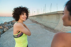 Två le konditionkvinnor som vilar, når att ha joggat utomhus Arkivfoton