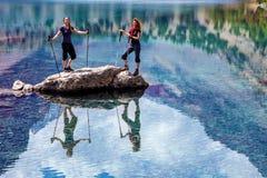 Två le kvinnlig som blir under den blåa berg sjön Royaltyfria Bilder