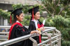 Två le kvinnliga asiatiska studenter i avläggande av examenkappa royaltyfri foto