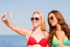 Två le kvinnor som gör selfie på stranden Royaltyfria Foton