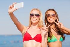 Två le kvinnor som gör selfie på stranden Royaltyfri Fotografi