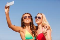 Två le kvinnor som gör selfie på stranden Royaltyfri Bild