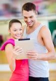 Två le personer med minnestavlaPC i idrottshallen Royaltyfri Foto