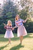 Två le roliga Caucasian flickasystrar i tyll för plädskjorta och rosa färgballerinakjolkringgår Arkivbilder