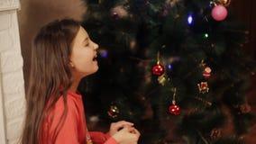 Två le små flickor som hemma dekorerar julpynt på träd för nytt år Julgran med gran-kotten nytt lager videofilmer