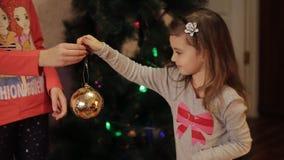 Två le små flickor som hemma dekorerar julpynt på träd för nytt år Julgran med gran-kotten nytt arkivfilmer