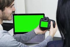 Två le tillfälliga formgivare som arbetar med bärbara datorn och minnestavlan i kontoret grön skärm Royaltyfri Bild