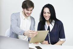 Två le tillfälliga formgivare som arbetar med bärbara datorn och minnestavlan i kontoret Manwoomanteamwork Royaltyfri Fotografi