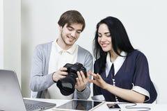 Två le tillfälliga formgivare som beskådar foto på kameran och bärbara datorn, minnestavla i kontoret Arkivbilder