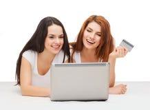 Två le tonåringar med bärbara datorn och kreditkorten Fotografering för Bildbyråer