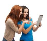Två le tonåringar med minnestavlaPCdatoren Royaltyfri Bild