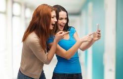 Två le tonåringar med smartphonen Royaltyfria Bilder