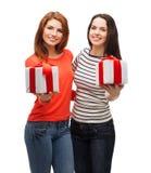 Två le tonårs- flickor med gåvor Fotografering för Bildbyråer