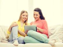 Två le tonårs- flickor med minnestavlaPC hemma Arkivfoton
