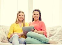 Två le tonårs- flickor med minnestavlaPC hemma Arkivfoto