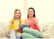 Två le tonårs- flickor med minnestavlaPC hemma Royaltyfri Fotografi