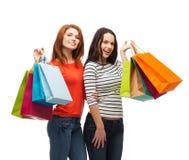 Två le tonårs- flickor med shoppingpåsar Arkivfoto