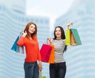 Två le tonårs- flickor med shoppingpåsar Arkivbild