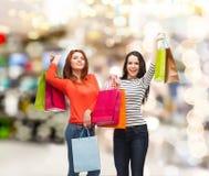 Två le tonårs- flickor med shoppingpåsar Arkivbilder