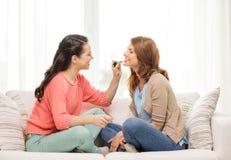 Två le tonårs- flickor som hemma applicerar smink Arkivbild