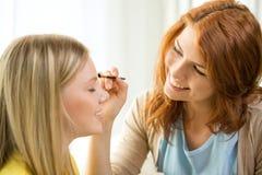 Två le tonårs- flickor som hemma applicerar smink Arkivfoto