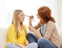 Två le tonårs- flickor som hemma applicerar smink Arkivfoton
