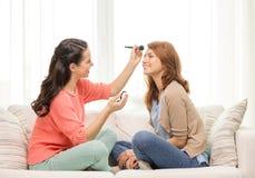 Två le tonårs- flickor som hemma applicerar smink Royaltyfri Foto