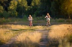 Två le tonårs- flickor som rider cyklar i fältet på solnedgången Fotografering för Bildbyråer