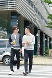 Två le unga affärsmän som går och talar i staden fotografering för bildbyråer