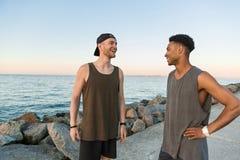 Två le unga grabbar i sportswear som talar, medan stå arkivbilder