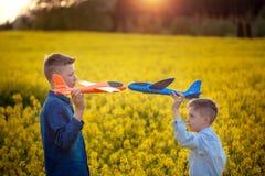 Två leksakerflygplan i handpojkar som ser de i gult fält på sommardag royaltyfria bilder