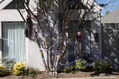 Två likätande onda andar hälsar tittaren av ett hus Arkivfoton