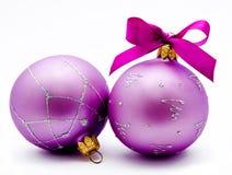 Två lila julbollar med det isolerade bandet Arkivfoto