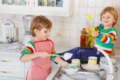 Två lilla älskvärda och roliga ungepojkar som tvättar disk i hemhjälp Arkivbilder