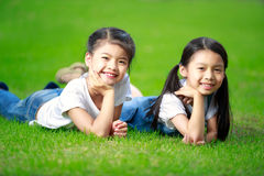 Två lilla asiatiska flickor som lägger på gräset Arkivbild