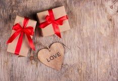 Två lilla askar med en röd pilbåge och valentin på den gamla träbakgrunden kopiera avstånd valentin för dag s Arkivfoto