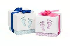 Två lilla askar med gåvan för ett nyfött behandla som ett barn, rosa färg- och blåttprickar, bästa som dekoreras med pilbågen Fotografering för Bildbyråer