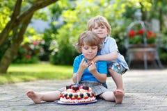 Två lilla barn som har gyckel samman med den stora födelsedagkakan Arkivbild