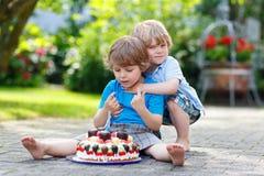 Två lilla barn som har gyckel samman med den stora födelsedagkakan Royaltyfri Bild