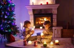 Två lilla barn som hemma sitter vid en spis på jul arkivbilder