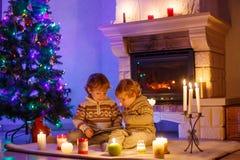 Två lilla barn som hemma sitter vid en spis på jul Royaltyfria Bilder