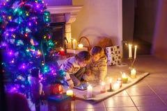 Två lilla barn som hemma sitter vid en spis på jul Arkivfoto