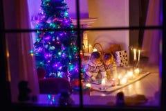 Två lilla barn som hemma sitter vid en spis på jul Arkivfoton