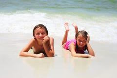 Två lilla barn som vilar på stranden och att le Royaltyfria Bilder